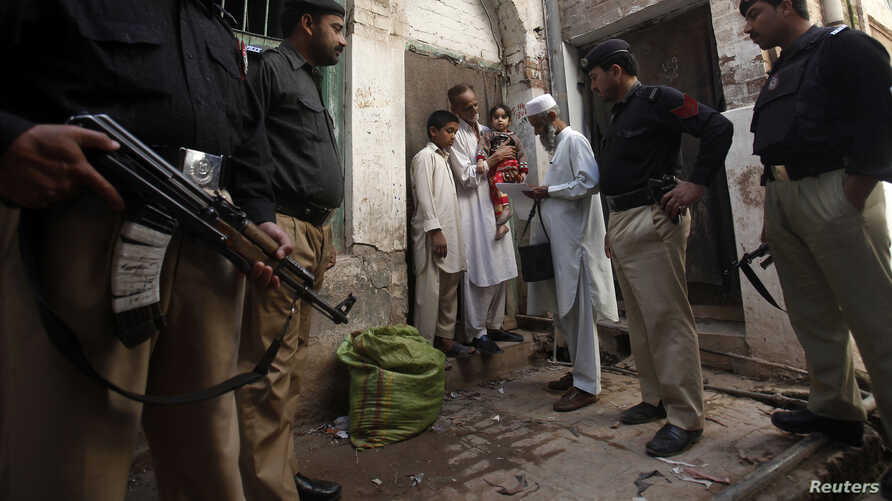 Police stand guard as a polio worker waits to give polio vaccine drops to children at a street in Peshawar, the capital of Khyber-Pakhtunkhwa province, Pakistan, March 30, 2014.