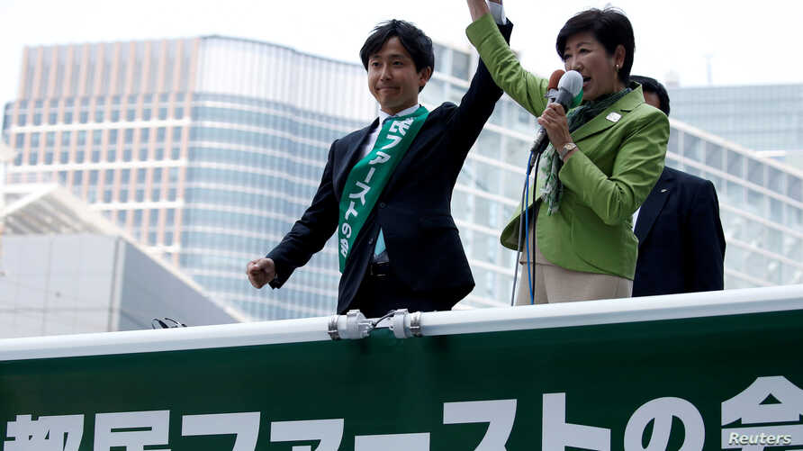 FILE : Tokyo Governor and head of Tokyo Citizens First party Yuriko Koike (R) delivers a speech to voters atop of a campaign van as election campaign officially kicks off for Tokyo Metropolitan Assembly election, on the street in Tokyo, June 23, 2017