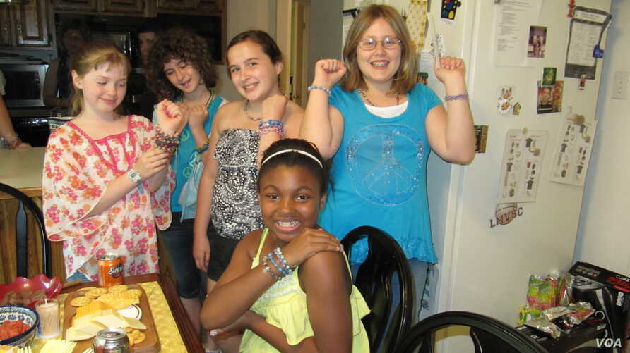 Madison Blandford (far left) and her classmates and neighbors show off their Ugandan beads at Madison's recent jewelry party. (VOA/F. Elmasry)