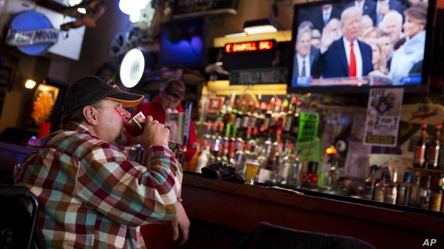 Jeff Dull watches as President Donald Trump is sworn in during a live broadcast of the inauguration at the Sawmill Saloon in Prairie du Chien, Wis., Jan. 20, 2017.