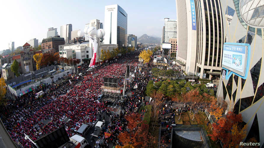 """South Koreans shout slogans as they carry placards reading """"Park Geun-hye Out,"""" during a protest against South Korean President Park Geun-Hye in Seoul, South Korea, Nov. 12, 2016."""