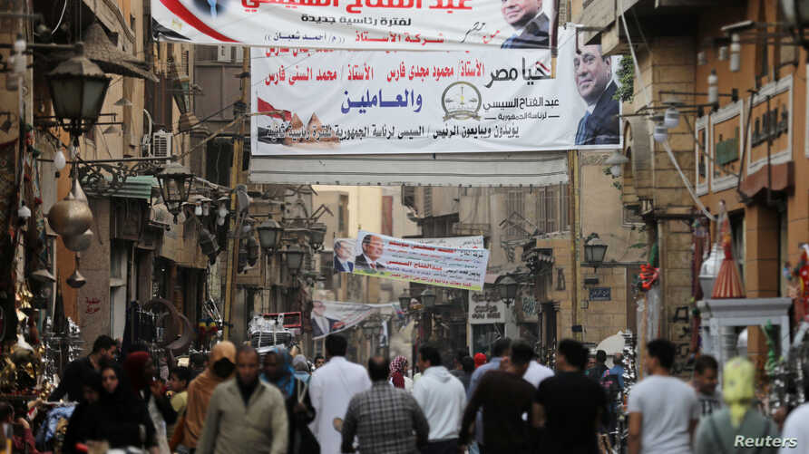 People walk under posters of Egyptian President Abdel Fattah al-Sissi for the upcoming presidential election, in Cairo, Egypt, March 19, 2018.