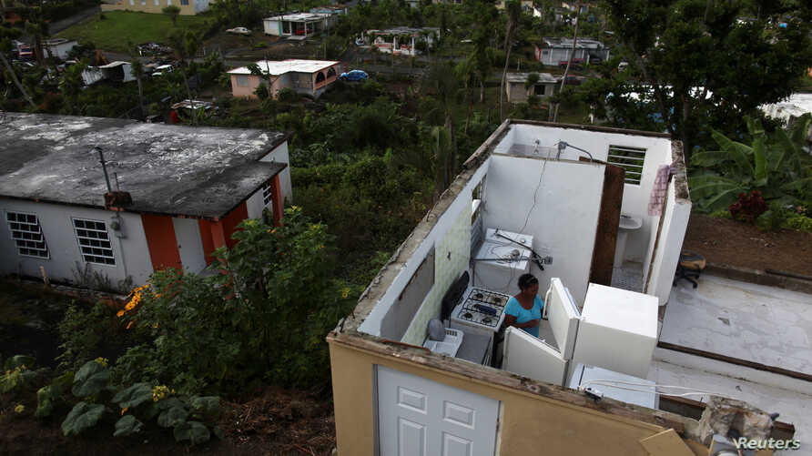Ernestina Lebron looks at her refrigerator while standing in her home, after Hurricane Maria hit the island in September 2017, in Maunabo, Puerto Rico, Jan. 27, 2018.