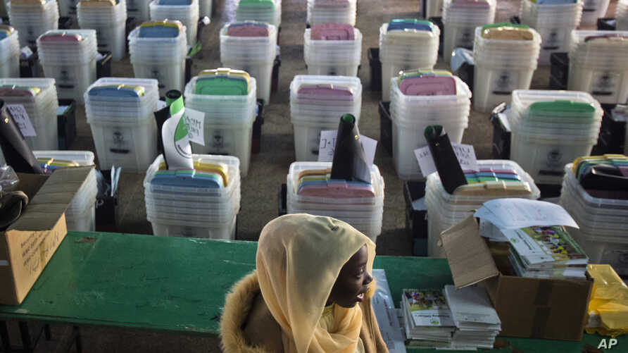 A Kenyan election volunteer walks past ballot boxes and electoral material to be distributed to various polling stations in Nairobi, Kenya, Aug. 7, 2017. Kenyans are due to go to the polls on Aug. 8. to vote in a general election.