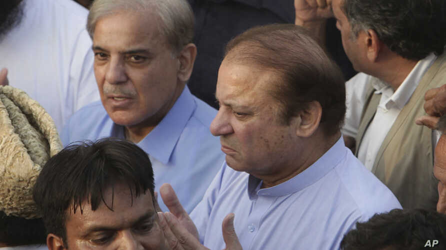 FILE - Pakistani jailed former minister of Pakistan Nawaz Sharif (C) prays during a funeral of his wife Kulsoom Nawaz with his brother Shahbaz Sharif in Lahore, Pakistan, Sept. 14, 2018.
