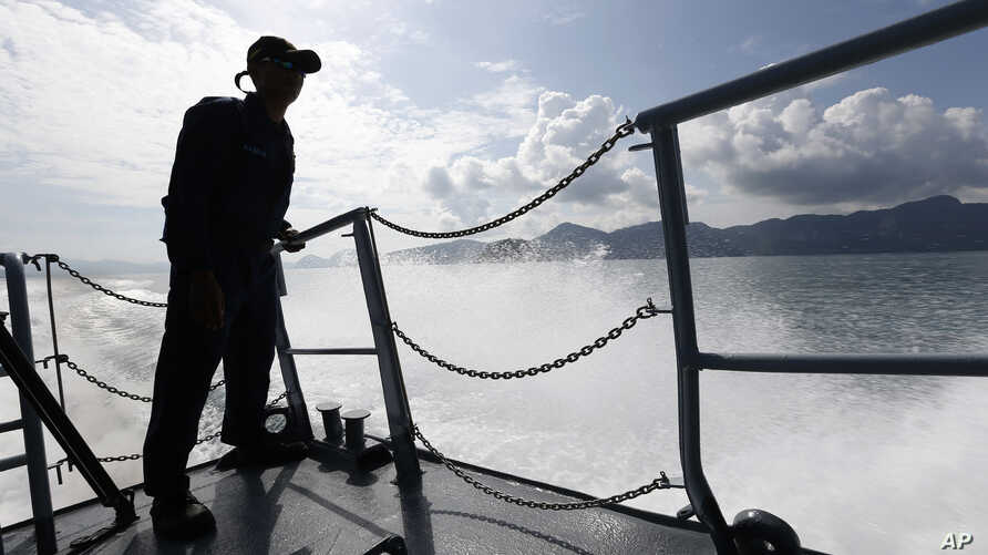 A member of Malaysian Navy is silhouetted as he stands guard on the bow of a corvette ship during a media trip for the search and rescue mission of Rohingya migrants in Langkawi, Malaysia on Thursday, May 28, 2015.