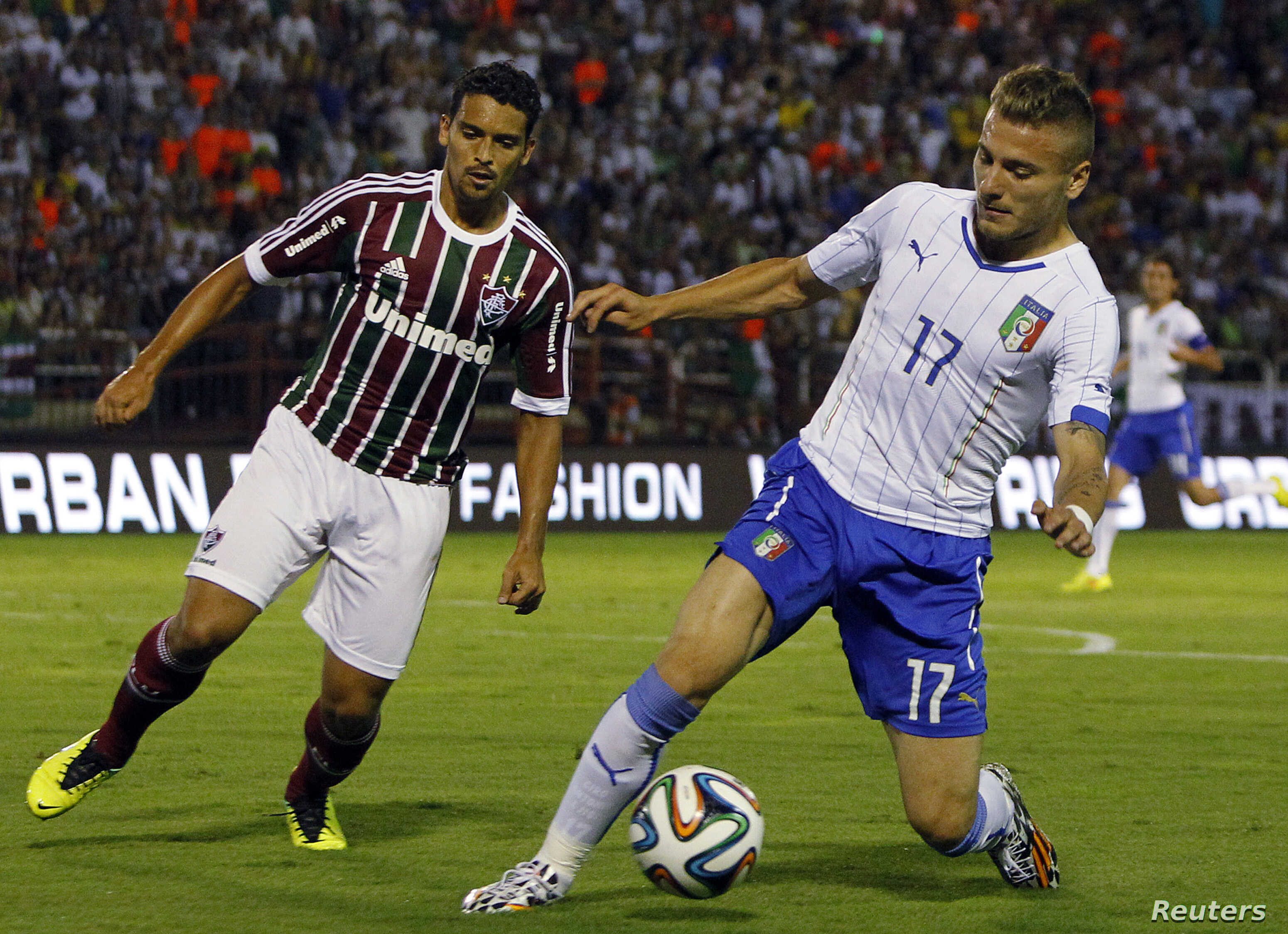 Italy's Ciro Immobile (R) fights for the ball with Fluminense's Jean during a friendly soccer match ahead of the 2014 World Cup at the Cidadania stadium in Volta Redonda, Rio de Janeiro state, Brazil, June 8, 2014.