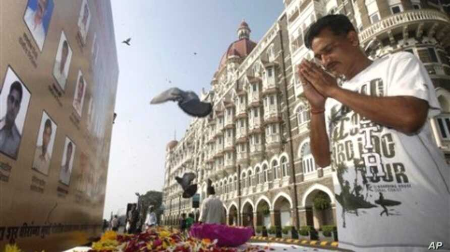 A man pays homage in front of portraits of police officers killed in the Mumbai terror attack outside the Taj Mahal Palace hotel, one of the sites of the attack, on the second anniversary of the attack in Mumbai, 26 Nov 2010