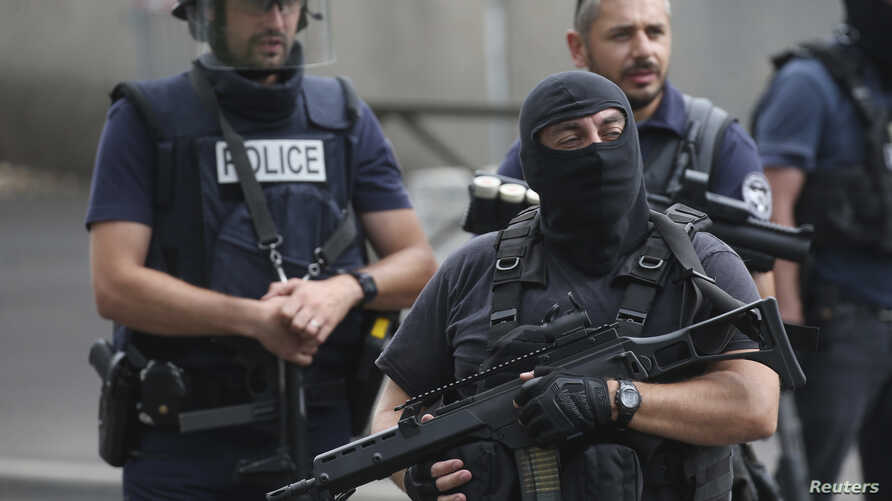 FILE - French police and anti-crime brigade members secure a street during a counterterrorism swoop at different locations in Argenteuil, a suburb north of Paris, July 21, 2016.