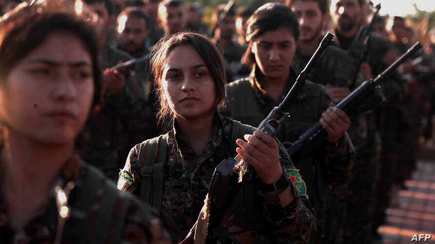 Fighters from the Syrian Democratic Forces attend the funeral a fellow fighter killed in the town of Hajin during battles against the Islamic State group, in the Kurdish-controlled city of Qamishly in northeastern Syria, on Dec. 3, 2018.