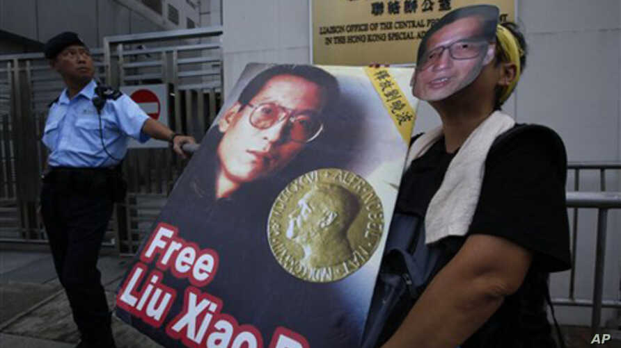 A pro-democracy protester wears a mask and holds a picture of Chinese dissident Liu Xiaobo while demanding Liu's release outside China's Liaison Office in Hong Kong, 11 Oct 2010