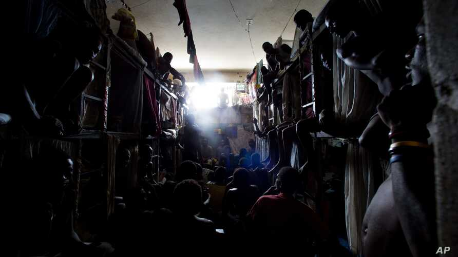 Prisoners cram shoulder to shoulder to watch TV in their crowded cell inside the National Penitentiary in downtown Port-au-Prince, Haiti, Feb. 13, 2017.