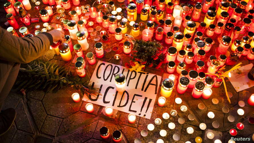 "FILE - A banner reading ""Corruption kills"" is seen among candles, lit in memory of dozens of people killed in a night club fire in Bucharest, at a memorial in Timisoara, Romania, Nov. 1, 2015. Officials who secured an operating license for the club,"