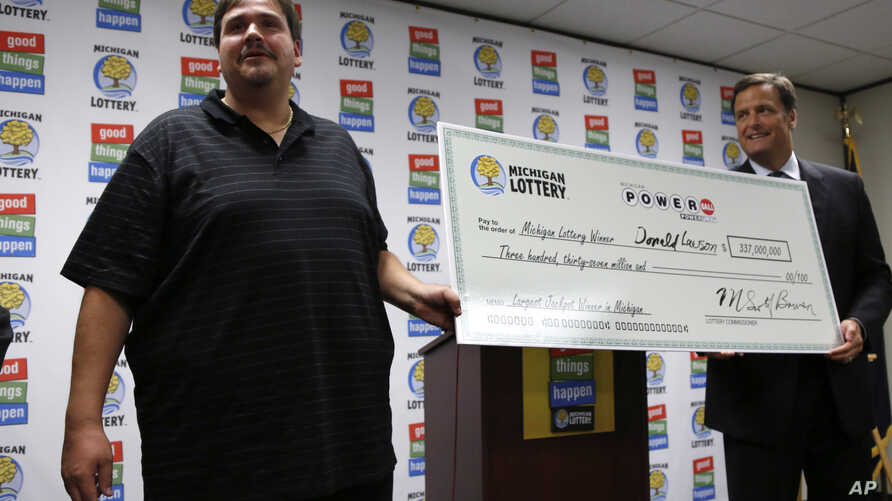 Donald Lawson holds his ceremonial check with Michigan Lottery Commissioner M. Scott Bowen at a news conference at the Michigan Lottery headquarters in Lansing, Michigan, August 31, 2012.