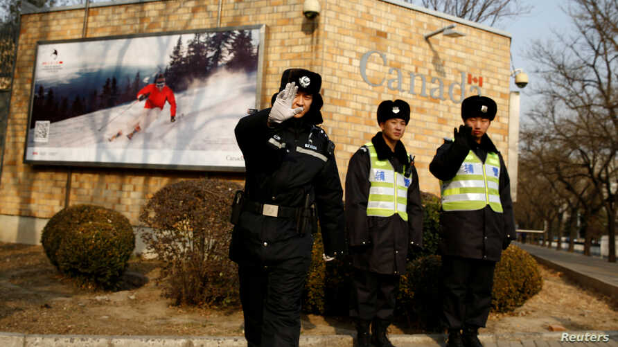A police officer gestures at the photographer as security staff stand guard outside the Canadian embassy in Beijing, Dec.r 20, 2018.