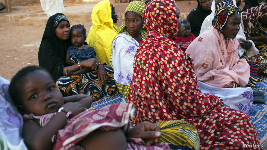 FILE - Displaced people are seen gathered at a house in Bamako February 21, 2014.