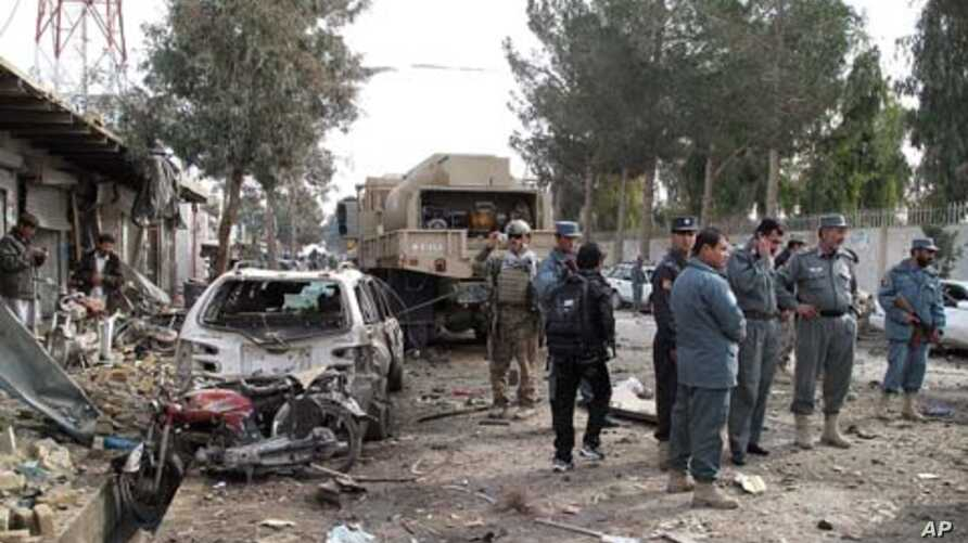 Afghan policemen investigate the scene of a deadly attack in Lashkar Gah, Helmand province on January 26, 2012. A suicide car bomber targeted a NATO convoy of armored vehicles, killing four people and wounding dozens of others.