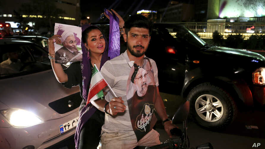 A supporter of the Iranian presidential candidate Ebrahim Raisi, right, holds his poster and the country's flag as his fiancee holds a poster of President Hassan Rouhani during a street campaign ahead the May 19 presidential election in downtown Tehr