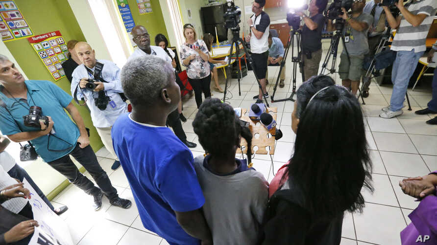 A Haitian family that did not want to be identified, living in the U.S. with Temporary Protected Status (TPS) speaks to members of the media, May 22, 2017, in Miami.