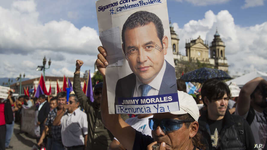 A man holds up a campaign poster of Guatemala's President Jimmy Morales during a gathering to show support for the Commissioner of the United Nations International Commission Against Impunity, Ivan Velasquez in Guatemala City, Saturday, Aug. 26, 2017