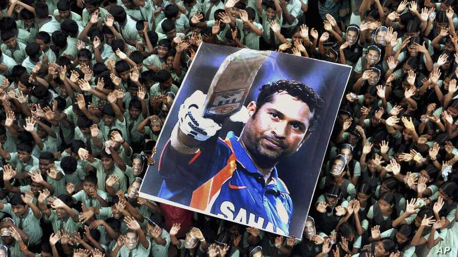 FILE - Indian students hold a large poster of Indian cricketer Sachin Tendulkar after Tendulkar batted for his landmark 100th century, Mar. 16, 2012.