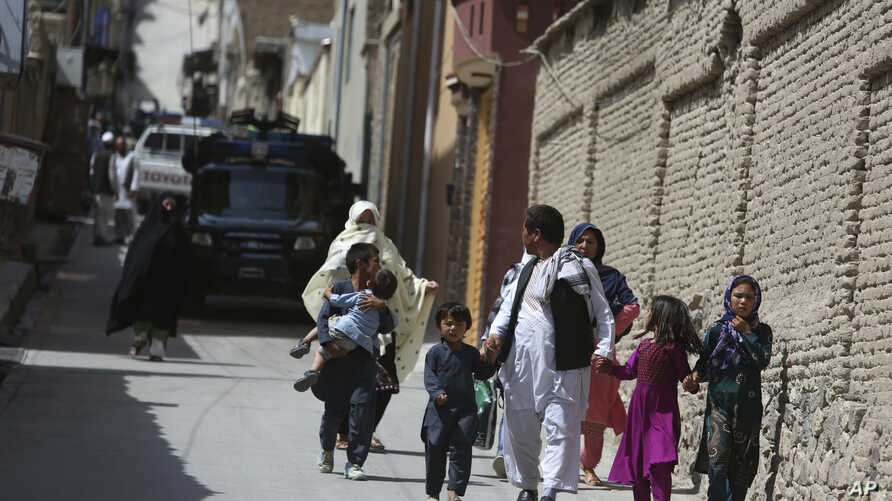 Families leaves their homes after a rocket strike in the western part of Kabul, Afghanistan, July 24, 2018.