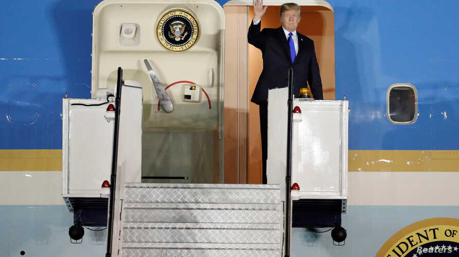 U.S. President Donald Trump waves upon his arrival at Paya Lebar Air Base in Singapore, before his summit with North Korean leader Kim Jong Un, June 10, 2018.