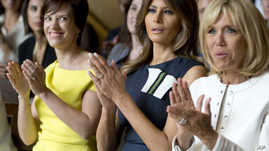 Amelie Derbaudrenghien, the partner of Belgian Prime Minister Charles Michel, left, U.S. first lady Melania Trump, center, and French first lady Brigitte Macron applaud during at the Queen Elisabeth Music Chapel in Waterloo, Belgium, July 11, 2018.