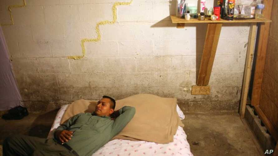 Toribio Jimenez lies on his bed in his basement bedroom of the home where he and 10 other people live in Nashville, Tenn, Sept. 3, 2009. Jimenez was given a job removing asbestos in the U.S. through the H2-B nonagricultural guest worker program. The