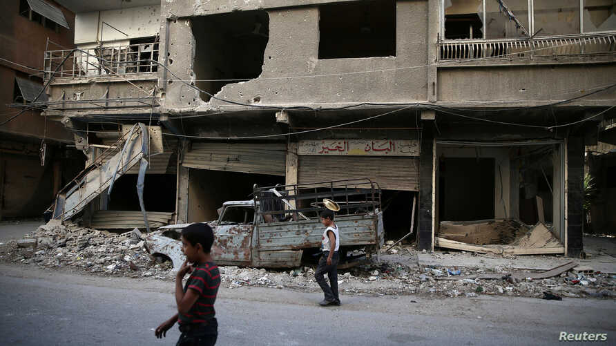 Children walk near damaged buildings in rebel-held Ain Tarma, eastern Damascus suburb of Ghouta, Syria, September 17, 2016.
