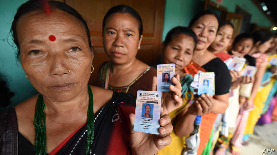 Indian voters pose for a photograph with their identity cards as they queue to cast their ballots in the state assembly elections at a polling station in Diphu in the Karbi Anglong district some 215 kms from Guwahati on April 4, 2016.