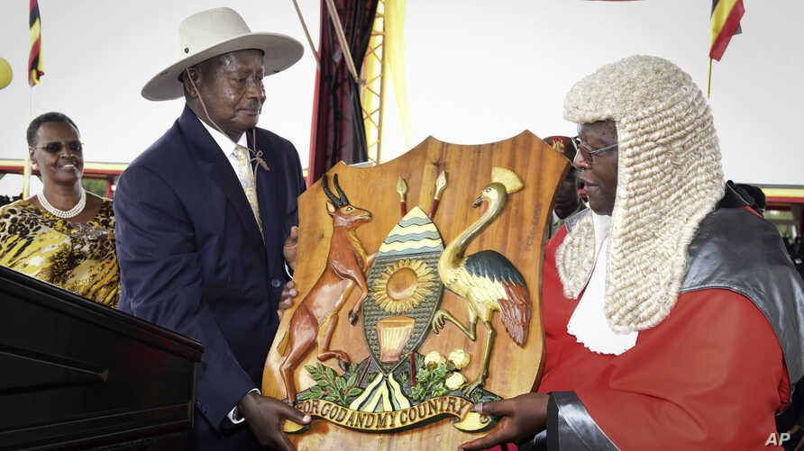 Uganda's long-time president Yoweri Museveni, 71, center left, receives a shield as a symbol of power from Chief Justice Bart Katureebe, right, as his wife Janet Museveni, left, looks on during an inauguration ceremony in the capital Kampala, Thursda...