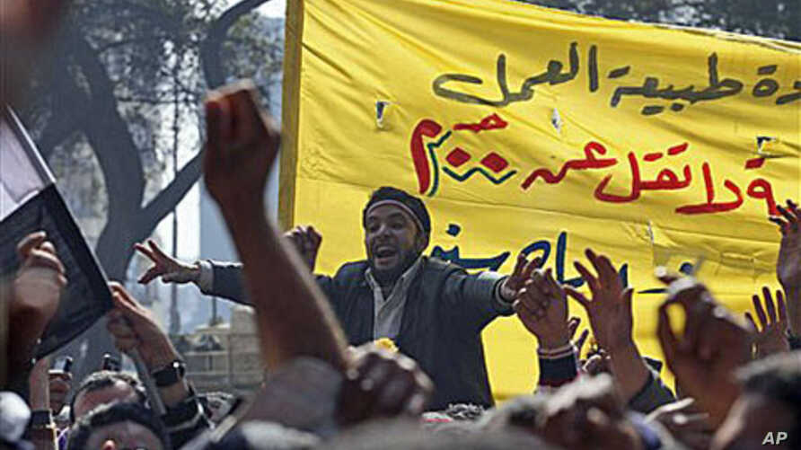 Public transportation workers protest in demand of salary raises in front of the national TV building, right, in Cairo, Egypt, February 14, 2011