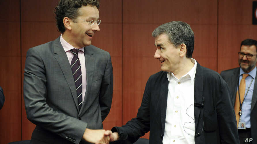 Dutch Finance Minister and chairman of the eurogroup Jeroen Dijsselbloem, left, shakes hands with Greek Finance Minister Euclid Tsakalotos during a meeting of eurozone finance ministers at the EU Council building in Brussels, Aug. 14, 2015.
