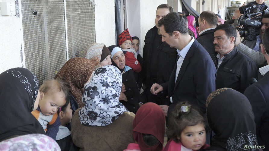 Syria's President Bashar al-Assad (C) speaks with women during his visit to displaced Syrians in the town of Adra in the Damascus countryside March 12, 2014, in this handout photograph released by Syria's national news agency SANA. State television s
