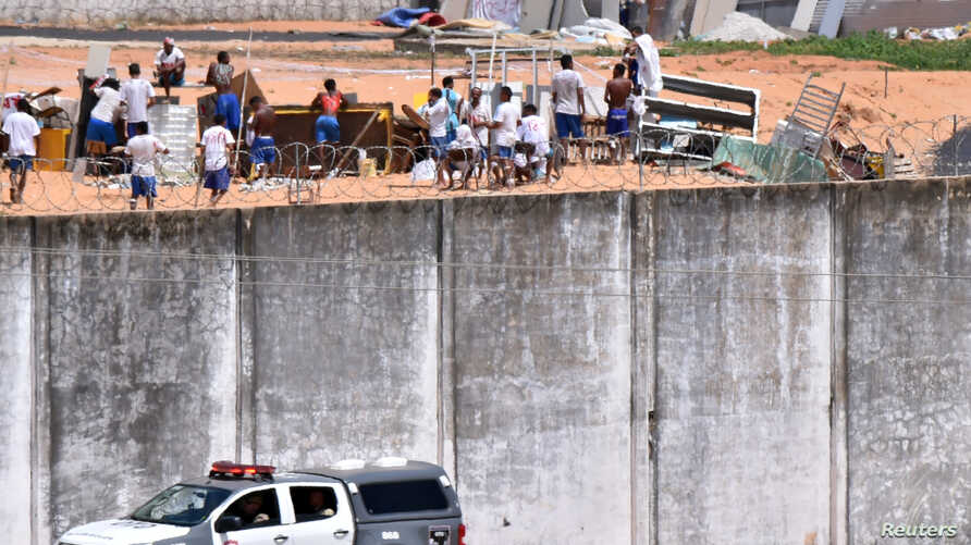 A police car drives past the wall of Alcacuz prison while inmates from different gangs, left and right, protect themselves during an uprising, in Natal, Rio Grande do Norte state, Brazil, Jan. 17, 2017.