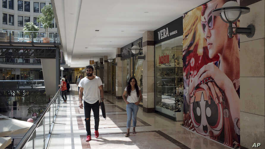 People walk in a shopping mall in Ankara, Turkey, Aug. 15, 2018. Turkey announced increased duties on U.S. products, including cars, tobacco and alcohol, on Wednesday in retaliation against U.S. sanctions and tariffs on Turkey in a continuing feud ov