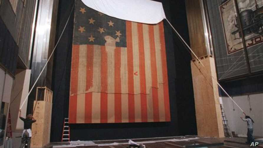 """In this Nov. 20, 1998 file photo, workers at the Smithsonian's National Museum of American History cover the flag that inspired """"The Star Spangled Banner,"""" prior to the flag's restoration."""