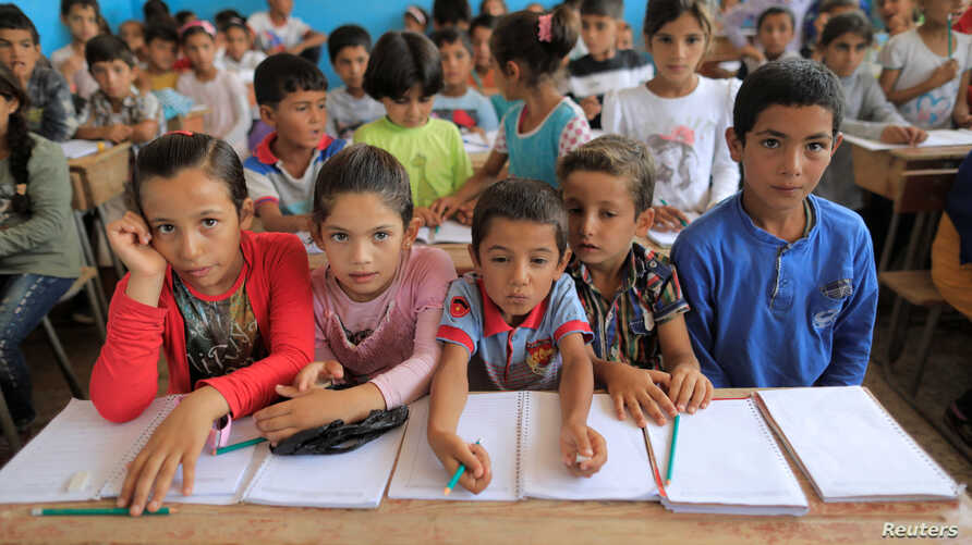 Children attend their first class immediately after they got registered at the school in Hazema North Raqqa, Syria, Aug. 21, 2017.