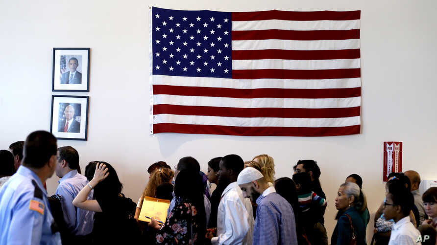 FILE - People file past the U.S. flag and a portrait of President Barack Obama on their way to attend a naturalization ceremony in Irving, Texas, July 3, 2014.