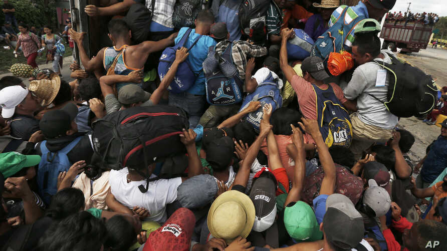 Central American migrants, part of one of the caravans hoping to reach the U.S. border, scramble to get a ride on a truck, in Isla, Veracruz state, Mexico, Nov. 3, 2018. The 150 buses that the governor of Veracruz promised to the migrants to get to M