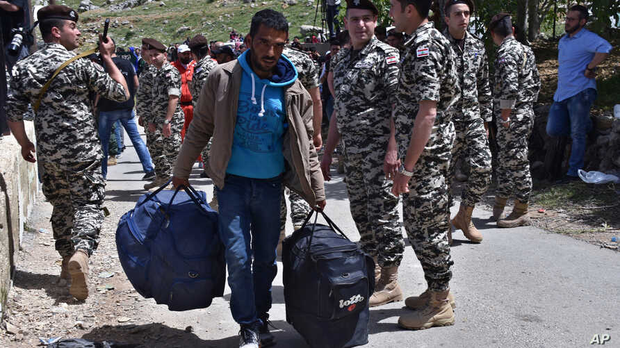 FILE - In this  April, 18, 2018 photo, a Syrian displaced man, who fled the war in Syria, carries his belongings past Lebanese General Security soldiers, as he prepares to return to his village of Beit Jinn in Syria, near the Lebanese-Syrian border,