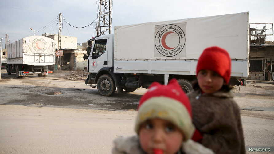 Children stand along a street as an aid convoy of Syrian Arab Red Crescent and United Nation (UN) drives through the rebel held besieged city of Douma towards the besieged town of Kafr Batna to deliver aid, on the outskirts of Damascus, Syria, Feb. 2...