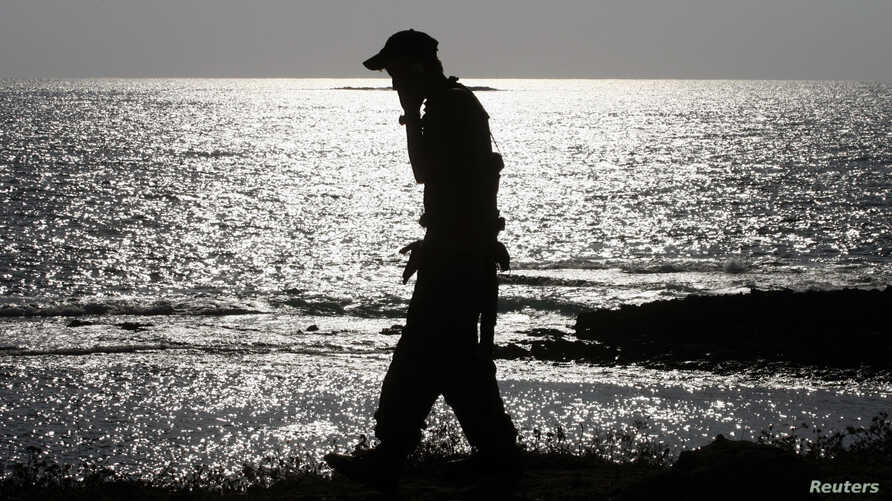 FILE - An Israeli soldier speaks on a mobile phone with his mother while walking alongside a beach near the city of Nahariya.