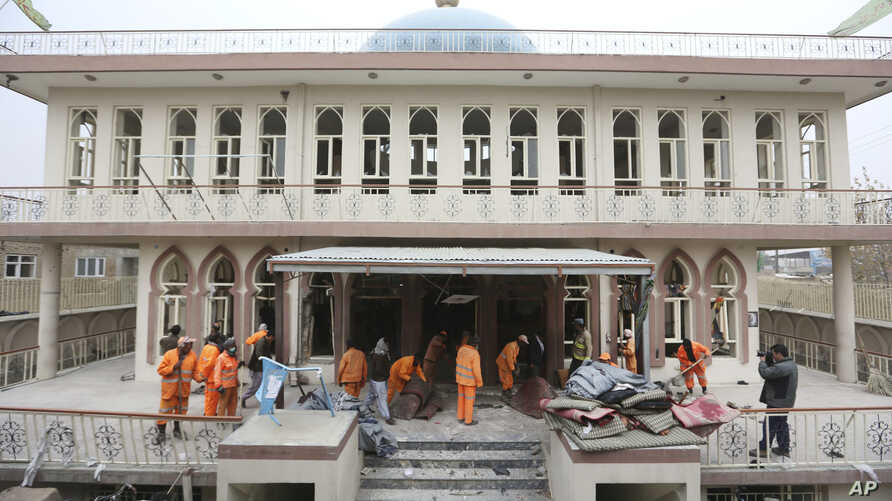 Afghan Municipality workers sweep Baqir-ul Ulom mosque after a suicide attack, in Kabul, Afghanistan, Nov. 21, 2016.