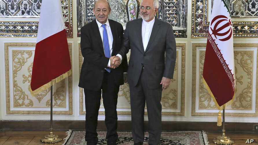 Iranian Foreign Minister Mohammad Javad Zarif, right, and his French counterpart Jean-Yves Le Drian, shake hands for journalists at the start of their meeting in Tehran, March 5, 2018.