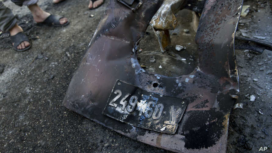 Palestinians inspect abandoned parts with the registration plate of an Israeli army vehicle that was burned during an Israeli army raid in the West Bank refugee camp of Qalandia, at the outskirts of Ramallah, March 1, 2016.