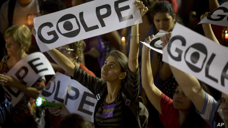 """A demonstrator holds a sign that reads in Portuguese """"Coup"""" during a protest against the impeachment of Brazil's President Dilma Rousseff, in Rio de Janeiro, Brazil, Tuesday, May 10, 2016."""