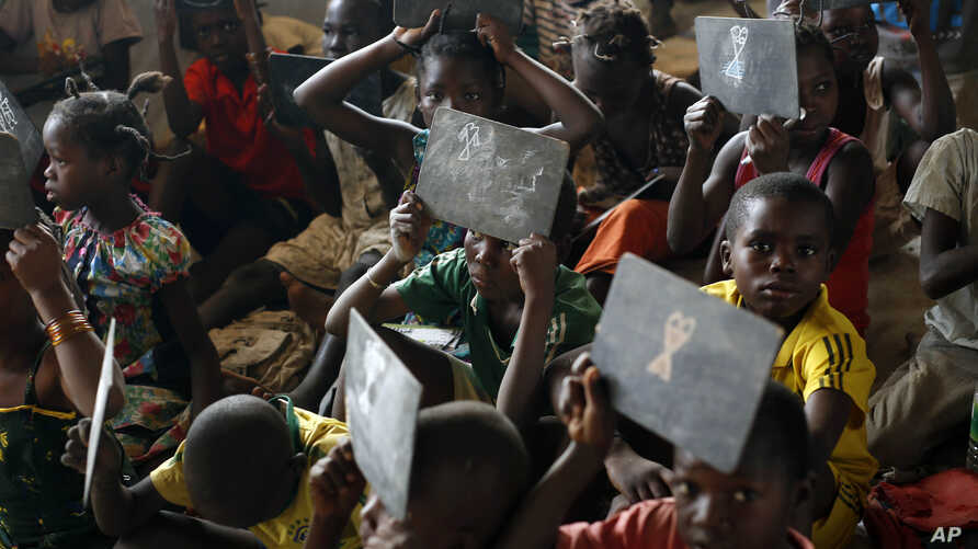 FILE - Children show their drawings to the teacher in a school set in the Mpoko refugee camp near the airport in Bangui, Central African Republic, Feb. 15, 2016.