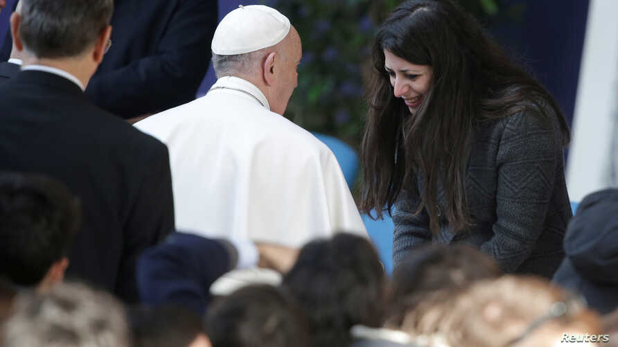 Pope Francis is welcomed by Nour Essa, a Syrian refugee, as he arrives to attend a meeting at Roma Tre University in Rome, Italy, Feb. 17, 2017.